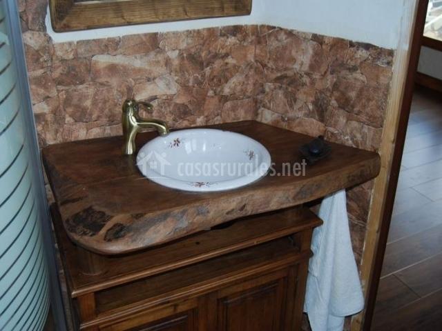 Aseo con encimera de madera y pila pintada a mano junto a la ducha
