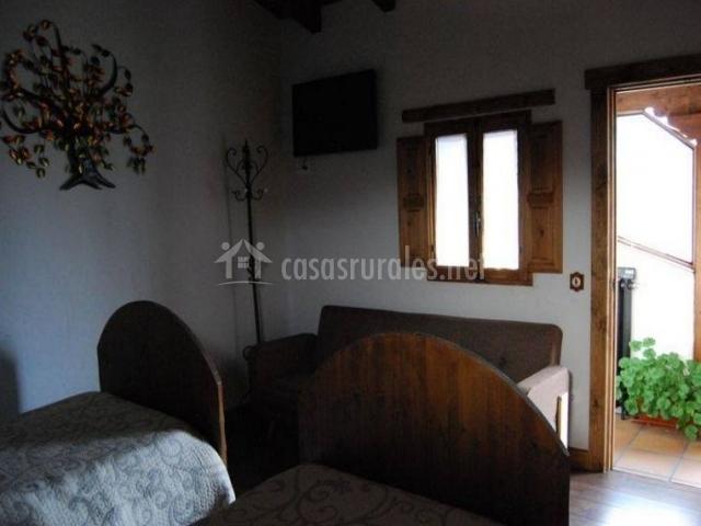 Dormitorio con un par de camas y sofá junto a la cpuerta