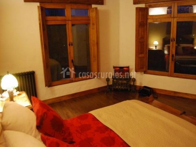 Dormitorio de matrimonio con ventanas frente a la cama
