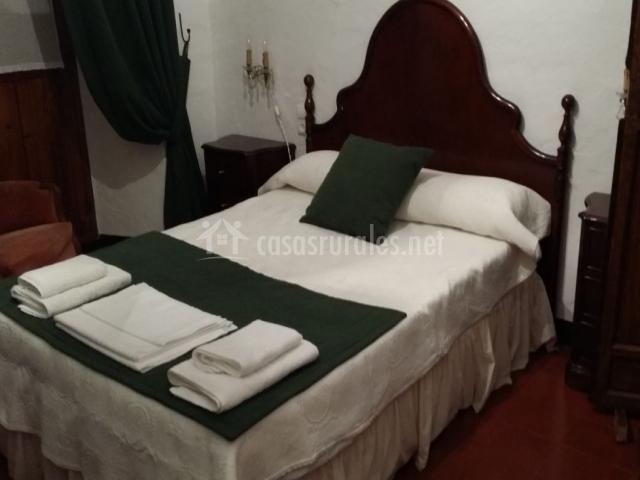 Dormitorio de matrimonio con toallas sobre la colcha