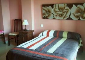 Dormitorio de matrimonio con cuadro de flores en la parte superior