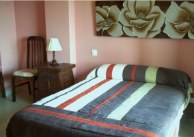 Dormitorio de matrimonio con cuadro de flores