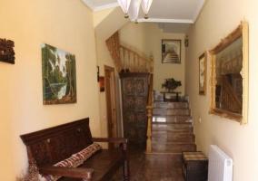 Hall recibidor con banco de madera tallada
