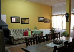 Sala de estar y comedor con chimenea y paredes en amarillo