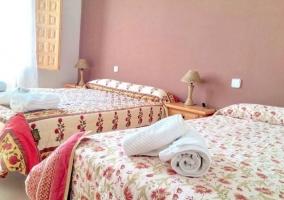 Dormitorio con detalles florales en los edredones