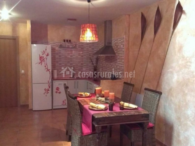 Cocina y mesa de comedor en espacio comunicado