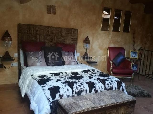 Dormitorio de matrimonio con manta de vaca