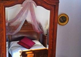 Dormitorio de matrimonio con cabecero de madera tallada