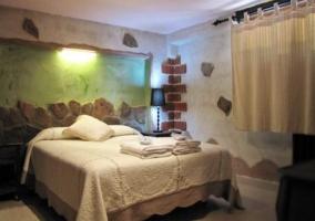 Dormitorio rústico con cama de matrimonio