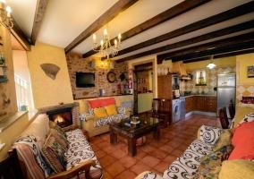 Sala de estar y cocina con chimenea de leña
