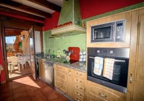Cocina con frente en verde y muebles de madera