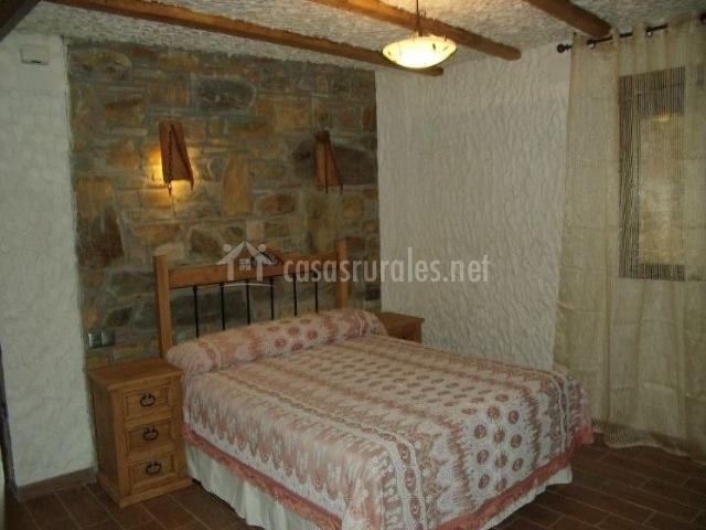 Dormitorio de matrimonio con frente de piedra y mesillas de madera