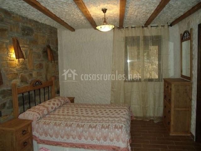 Dormitorio de matrimonio con frente de piedra