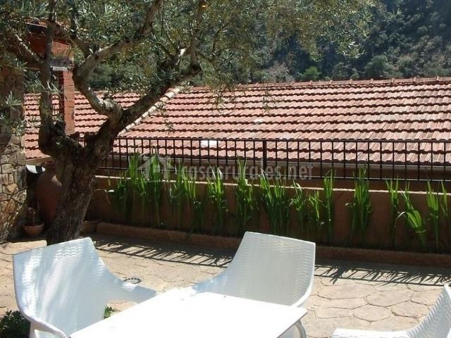 Vistas de la terraza equipada con mesa y sillas blancas