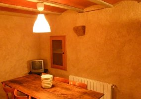 Comedor con lámpara sobre la mesa de madera