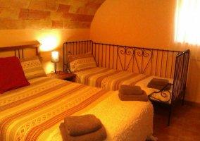 Dormitorio abovedado con colchas de rayas