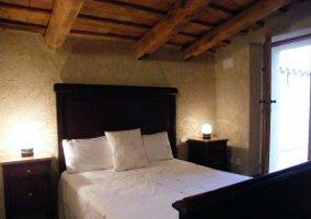Dormitorio de matrimonio con cabecero alto y oscuro
