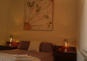 Dormitorio de matrimonio con cuadro floral sobre la cama
