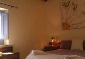 Dormitorio de matrimonio con cuadro floral