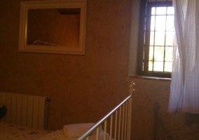 Dormitorio de matrimonio en tonos claros y cama junto a la ventana
