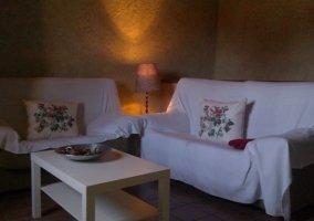 Sala de estar con televisor de plasma y sillones en blanco