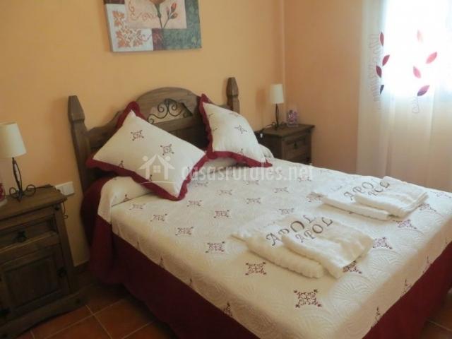 Dormitorio de matrimonio con colcha en burdeos