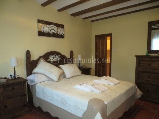 Dormitorio de matrimonio con colcha en marrones y blancos