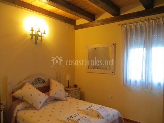 Dormitorio de matrimonio en tonos claros con toallas bordadas