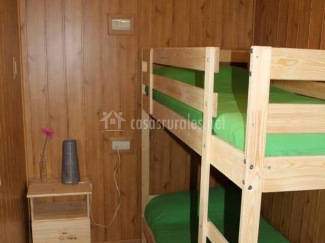 Dormitorio con camas en litera y friso de madera