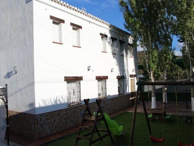Vistas de la fachada y columpios en el exterior