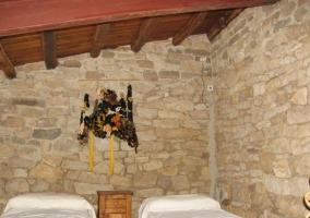 Dormitorio doble con paredes de piedra y techos abuhardillados