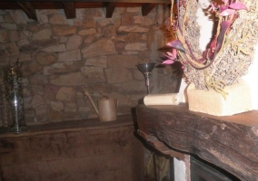 Sala de estar con chimenea encendida y repisa de madera
