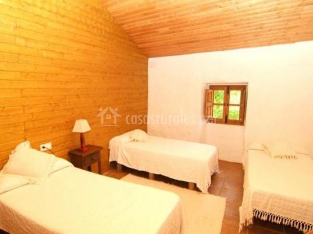 Dormitorio triple con colchas blancas y mesilla
