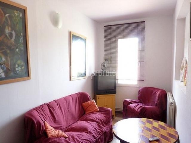 Sala de estar con sillones y televisor junto a la ventana