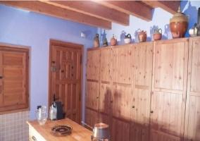 Cocina con armarios de madera y vasijas
