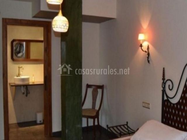 Dormitorio amplio con elegante cabecero y su aseo