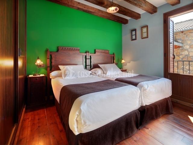 Dos camas individuales con cabecero de madera y pared verde