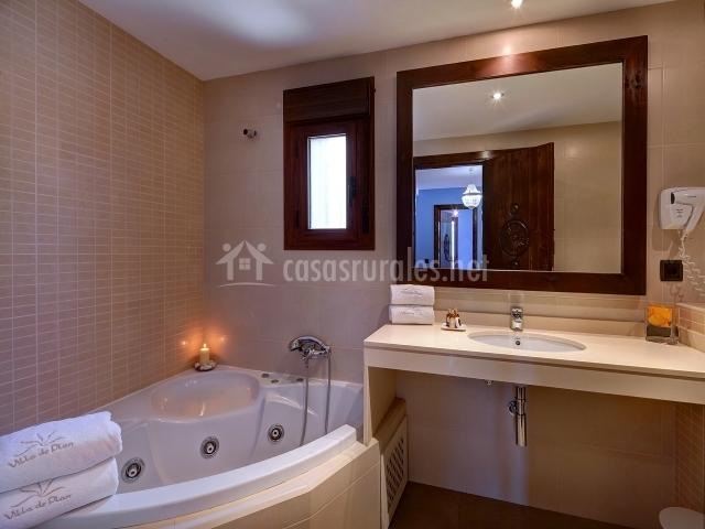 Bañera con hidromasaje en servicio que tiene un amplio espejo