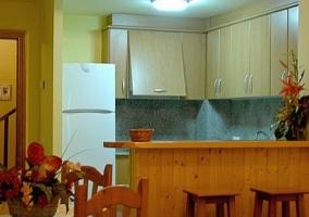 Cocina en L con armarios de madera y lavadora