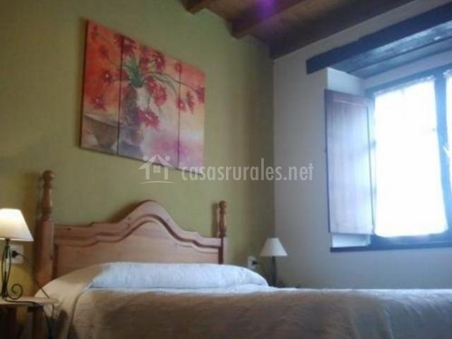 Dormitorio de matrimonio con ventana junto a la cama