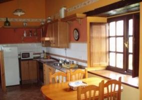 Cocina de aspecto rústico con mesa de madera