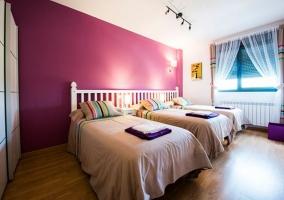 Dormitorio triple con pared morada