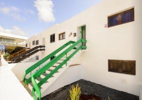 Acceso a la casa con escaleras en blanco y verde