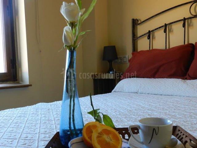 Dormitorio de matrimonio con colcha en blanco y cojines