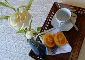 Dormitorio de matrimonio con colcha en blanco y desayuno