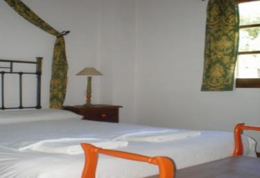 Dormitorio de matrimonio con banco a los pies de la cama