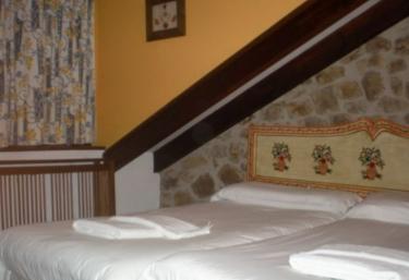 Dormitorio doble abuhardillado con pared de piedra