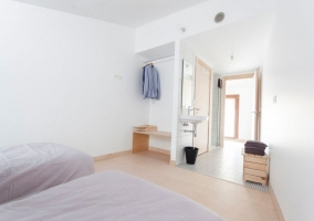 Dormitorio doble con camas individuales y aseo en el mismo espacio