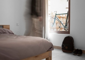 Dormitorio de matrimonio con cama junto a la cristalera