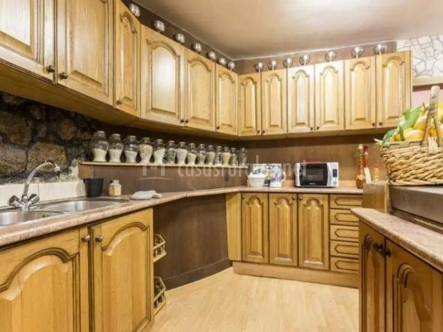 Cocina con armarios en madera y microondas